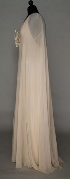 Christian Dior Haute Couture evening gown from spring 1974. Made from beige color triple layer chiffon crepe sheath, deep V front and back neckline, floating side panels, CF organza and velvet millinery  flower with a matching crepe chiffon single layer, floor lenght cape. #Christian #Dior House of Dior.