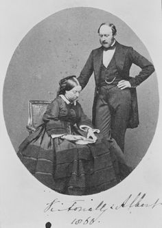 Photograph of Queen Victoria (1819-1901) and Prince Albert, Prince Consort (1819-1861). The Queen is reading a book, pointing something to the Prince who is looking down.