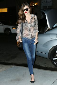 Miranda Kerr in a sheer blouse, jeans, and ballet flats.