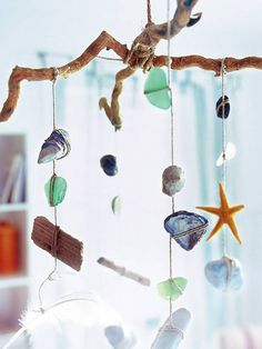 . Bind shells, stones and colored sea glass in colorful array of nylon cords and attach them to a piece of driftwood. Looks especially good in the bathroom or on the porch.