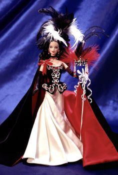 Illusion Barbie Masquerade Gala Collection Limited Edition Release Date: 1/1/1998 the first doll from a collection celebrating the mystery of a masquerade ball. Cloaked in a velvety cape of ebony, lined in scarlet satin. Silvery embroidery adorns her bodice while an ivory, pleated satin skirt adds contrast and drama. Her harlequin mask is adorned with feathers, Swarovski® crystals and hand-beaded tassels. A regal headdress of black and white feathers crowns her raven ringlets.