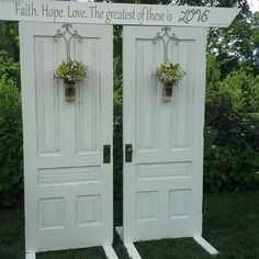 Wildflower-inspired flowers hang from two wooden doors as the backdrop for a ceremony. www.bloomtasticweddings.com