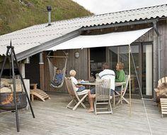 NATURLIG UTESTUE: Taket er trukket over en del av terrassen med en utebod i bakkant. En enkel solskjerm gir ly for sola.