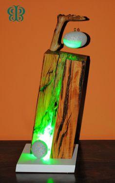 ACI - La lampada è realizzata in legno di ulivo inclinato e attraversato da un fascio di luce verde a led