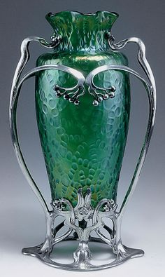 Loetz 'Diaspora' vase with metal frame, c1902. H. 36.4 cm. Green glass, bark-like wall, matt mother of pearl lustre.