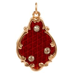 A two-part gold, enamel, and diamond locket, unrecorded maker's mark AS (Cyrillic), 1908-1917. Yellow gold scrolls encircle the patterned red translucent enamel which is set with three rose-cut diamonds. 6.5k USD
