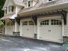 I love the little pergola above the garage. It would look even better with vines growing over it!