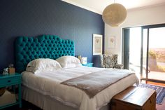 """The master bedroom. """"The blue-green bedroom thing started with a velvet corduroy in peacock blue that I found in a tucked away shop in Woodstock – for R20 a metre!! I bought 10 metres immediately and that was put to good work in making a deep buttoned headboard. I've always wanted a fancy, hotel style headboard and we both love this one,"""" says Vicki."""