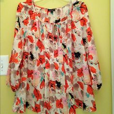Flowy Blouse. Floral print. Pleated in center with tie at keyhole neckline. 3/4 length sleeves with elastic at bottom of sleeve. 100% Polyester. Womyn Tops Blouses