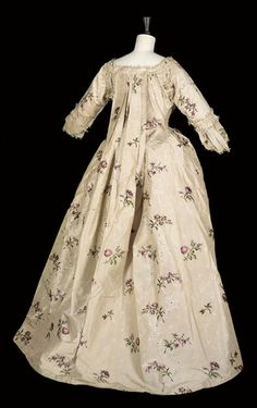 Rear view, robe à la francaise, 18th century. Shell pink silk brocaded with a purple floral sprig and heavily embellished with cream fly braid.