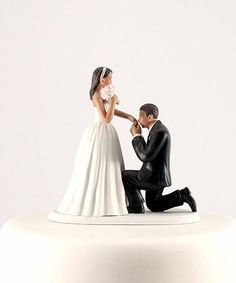 """A """"Cinderella Moment"""" Hispanic Couple Wedding Cake Topper made of hand painted porcelain.  The bride is wearing a beautiful princess style gown, a silver headpiece, and she is holding a bouquet of pink roses. The groom is on bended knee, wearing a handsome black suit, kissing his bride's hand."""