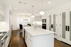 Long white kitchen features three Hudson Valley Lighting Lambert 1 Light Pendants illuminating a long center island fitted with a farmhouse sink and pull out faucet next to a dishwasher facing a wall of pantry cabinets accented with frosted glass doors.