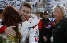 Carl Edwards gets a hug after winning the pole position for Sunday's NASCAR Sprint Cup series auto race at New Hampshire Motor Speedway, Friday, Sept. 25, 2015, in Loudon, N.H. (AP Photo/Jim Cole)
