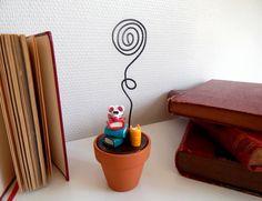 """Porte-photo """"rat de bibliothèque"""". Petit rat assis sur une pile de livres. La tige du porte-photo est un fil d'aluminium très souple permettant de maintenir n'importe quel format de papier (photo, carte de visite, petit mot, etc..)  Porte-photo """"rat de bibliothèque"""", le cadeau idéal pour une personne aimant lire !  #portephotooriginal #livres #patepolymere"""
