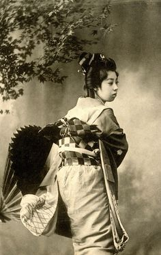 A Geisha dressed in the Genroku style, fashionable among Tokyo Geisha around 1905-1908. She is showing her obi, tied in the Kichiya-musubi style, a knot named after Kamimura Kichiya (or Uemura Kichiya I) who was a popular Kabuki Actor during the Genroku period (1680s).