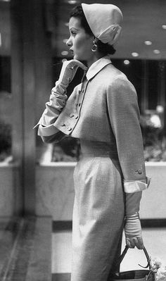 1953  Model posing in a train station wearing a stylish new fashion.