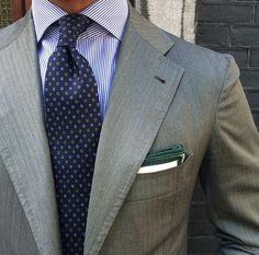 Grey suit. Navy tie.