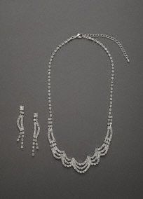 This elegant necklace and earring set is beautifully embellished with crystals. The scallop design of the necklace allows it to lay beautifully and complement any neckline. Accompanied by the the fun and fresh linear crystal earrings make this set stand out for sure. This gorgeous set is sure to make you look like you stepped right off the Red Carpet Glamour.  Crystal necklace features beautifully embellished scallop design.  Linear dangle post earrings finish off the look.  David's
