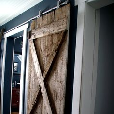 See how to install a hanging barn door for a master bathroom using an old one from a grandparents' wood shed. It is simpler than you'd expect! Grandma's House DIY featured on Kenarry.com