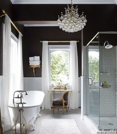 Annie Brahler - Stunning bathroom with dark chocolate walls paired with white board and batten, claw foot tub, polished nickel floor-mounted tub filler, crystal chandelier, walk-in glass shower with subway tile shower surround, white and gold French vanity with chocolate brown oval back French chair under window covered in white sheers on antique brass curtain rods.
