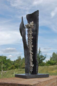 """Kleinplastik """"Paar, was sich sein Glück bewahrt"""", Stahl geschmiedet / Nickel, Höhe ca. 400 mm. Zwei geschmiedete Stahlelemente beherbergen eine strahlende Nickelstele in korallenähnlicher Form."""
