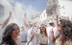Polvo para el pueblo! Juerguistas lanzan polvos de talco sobre la otra durante el carnaval anual de Los Indianos en Islas Canarias. Un juerguista mujer baila en la calle, como miles de otros tiran el polvo de talco