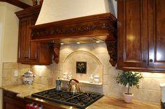 Carved moulding on hood, corbels, and picture frame tile back splash.