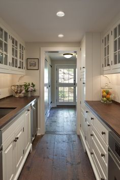 Stunning galley kitchen.  I love the simplicity of the cupboards against the dark backdrop of the timber floors.