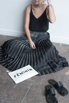 Meg Biram in black pleated skirt with white clutch at Longview Gallery in Washington DC.