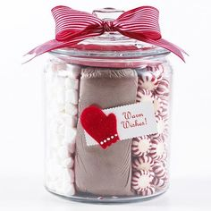 Bag of hot coco in the middle and marshmallows and mints around it in an empty glass jar with a tag on the out side