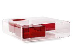 Michel BOYER (1935-2011) Table basse carrée en plexiglas translucide, ornée d'un casier supérieur et de deux casiers latéraux en plexiglas rouge carmin, profils quadrangulés à angles arrondis, plinthe en retrait. Les caissons sont soutenus par des cylindres en plexiglas. Haut. 35cm - Plateau: 100 x 100cm