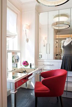 mirrors everywhere, amazing lighting, mirrored vanity table & electric red chair...perfection