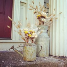 Outdoor spring decor. Vintage looking milk jug and watering can filled with dried neutral and yellow flowers. Christmas tree shoppe and Michael's.