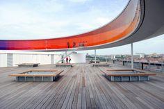 """Imagina poder enxergar o mundo de um arco-íris. Olafur Eliasson te dá essa possibilidade, pois ele é o autor de um tubo panorâmico construído no topo do prédio do Aros Aarkus Kunstmuseum, na Dinamarca.  Chamado de """"Your rainbow panorama"""" – seu arco-íris panorâmico, em tradução livre -, a colorida obra é uma circunferência com 52 metros de diâmetro, em 150 metros de corredor, com três metros de altura por três de largura, apoiada por 12 colunas de ferro."""