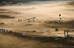 NO ES ESPEJISMO, ES LA NIEBLA DE LA MAÑANA  Parace otro lugar, otro Mundo. Tienes la sensación de estar de caravana por el interior del desierto, en lugar de arena el fondo es lava y volcanes. Así es el paisaje de Lanzarote, todo lleno de embrujos. No es un espejismo, es la niebla de la mañana.   Imagen de Gustavo Medina en Masdache, Tías, Lanzarote.
