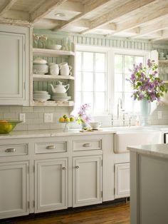 fill in gaps between window & cabinets with open shelves.  Put beadboard behind shelves & above window so can stop subway at backsplash height.  If doing a type of cornice above window .. could use beadboard also.