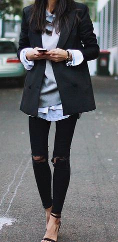 Ripped jeans paired with a sweatshirt layered under a classic blazer