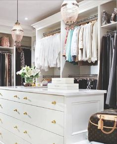 Elegant touches: chandelier lighting, gold hardware, crown molding. #walkin closet #closet