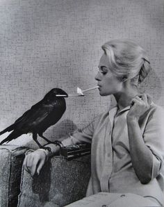 "Tippi Hedren gets her cigarette lit by a Raven, love this promo shot for Hitchcock's ""The Birds"""