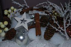 Ein Dekoteller mit ein paar Sternen, Kugeln und Zimt und Zapfen sind eine schöne Weihnachts Deko auf dem Tisch