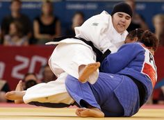Saudi Arabia's Wojdan Shaherkani fights with Puerto Rico's Melissa Mojica during their judo match at the London 2012 Olympic Games.
