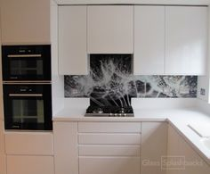 Dandelion clocks printed glass splashback. Fitted as part of our nation-wide Measure & Fit Service, this splashback was inspired by nature. Our design team resized the image to fit this clients specification. The finished article is dramatic and stylish.  Visit glasssplashbacks.com to discover more.