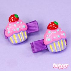 Want to feel as cute as a cupcake? Clip on these super scrumptious hairpins that feature a pink and purple cupcake topped with a bright red strawberry. The set includes two hairpins with fabric clips. Oh yumm!