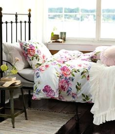 i love the contrast of the delicate flower comforter and the metal headboard.