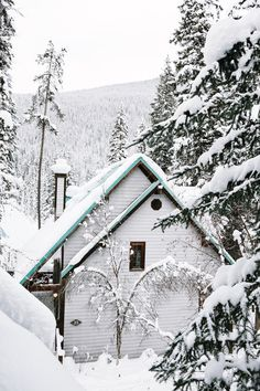A pretty traditional style ski chalet hidden in the trees on the snowy mountain side in the Italian Alps. The chalet is built of wooden paneling and painted white, with turquoise blue detailing and natural wood features.