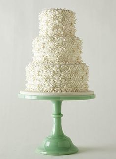 Beautiful white floral cake on a green cake pedestal