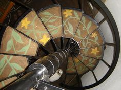 Cob on spiral stairs, painted with glauconite mineral and yellow oxide natural pigments.
