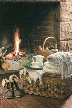 Cozy home. Still life of woman's boots, blankets and kettle in front fireplace. by Eduard Bonnin - Stocksy United - Royalty-Free Stock Photos