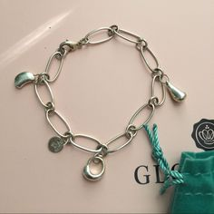 TIFFANY AND COMPANY ELSA CHARM BRACELET Missing two charms. Selling it because it came from an ex boyfriend and the relationship ended badly. Tiffany and Company Jewelry Bracelets
