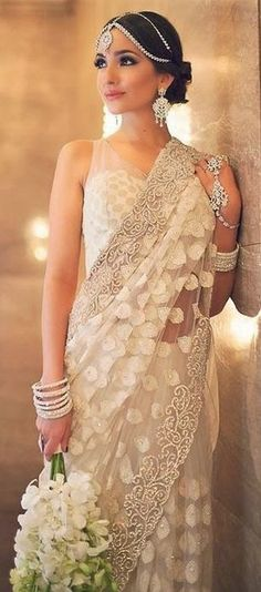 This beautiful bride is wearing a simple white sari with elegant embroidery on the border. This wedding saree is perfect for a fusion bridal saree; add some nice jewelry and it's so beautiful